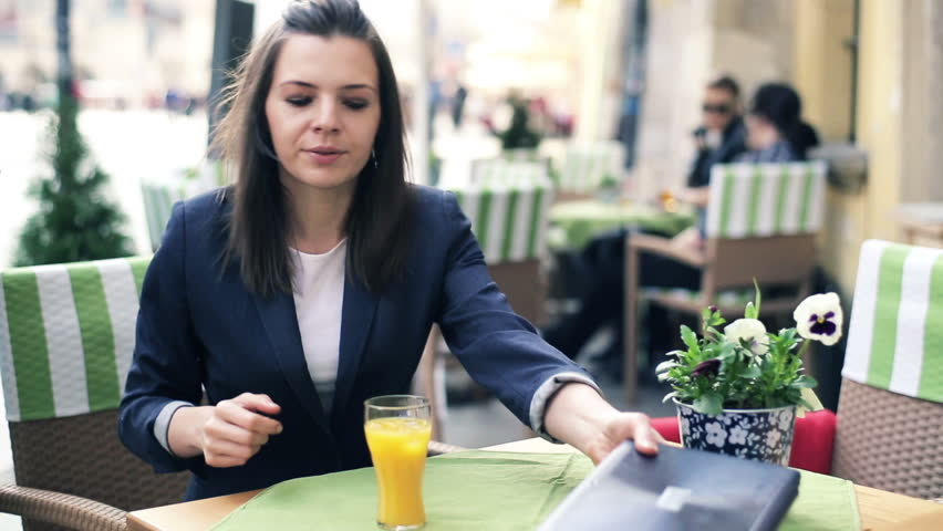 Young businesswoman gets lunch from waitress in outdoor restaurant