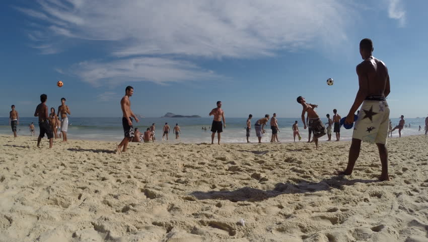 RIO DE JANEIRO, BRAZIL - FEBRUARY 9, 2014: Young Brazilian men play altinho keepy-uppy beach football in a circle on a bright afternoon at the Posto 9 section of Ipanema Beach.