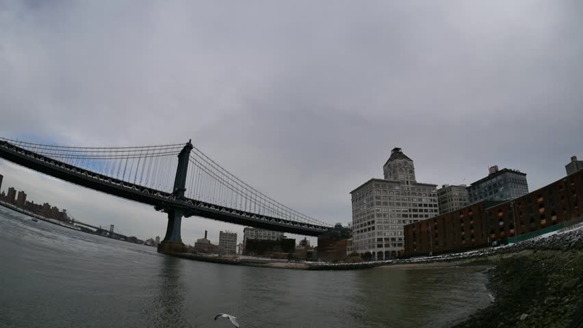 New York - March, 2014 - Slow motion fisheye shot panning from the Manhattan Bridge to the Brooklyn Bridge.