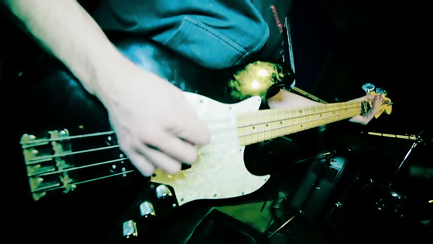 Male hands playing on electrical bass guitar