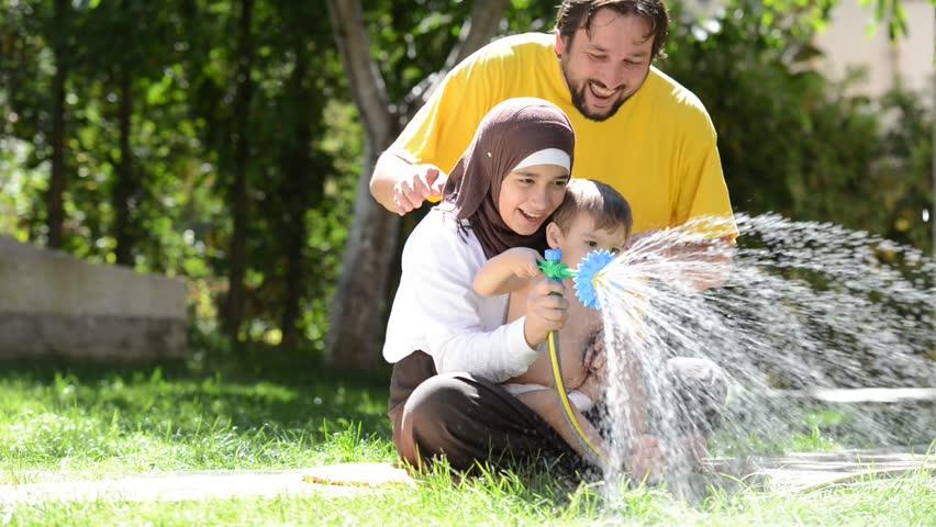 Happy children splashing with water sprinkler on summer grass
