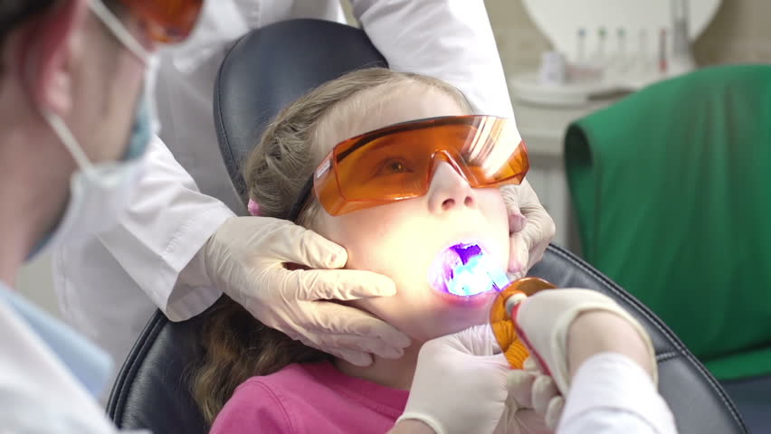 Full face of preteen patient at the recliner chair having her tooth cured with light by unrecognizable practitioner and assistant