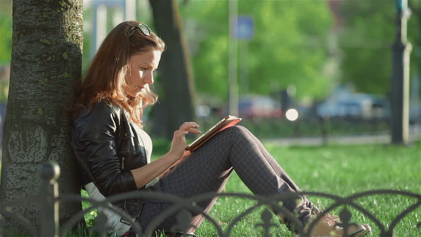 Girl sitting under a tree and uses tablet