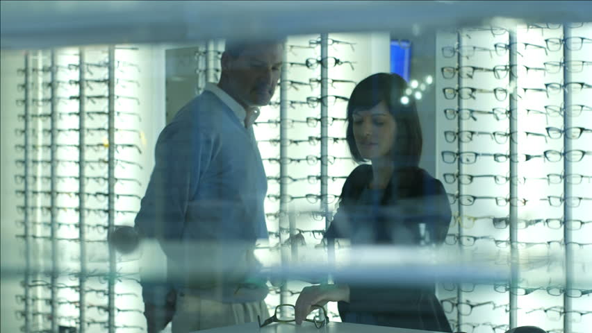 Female Optician guides and asssits Male patient to choose a new pair of glasses #6173213