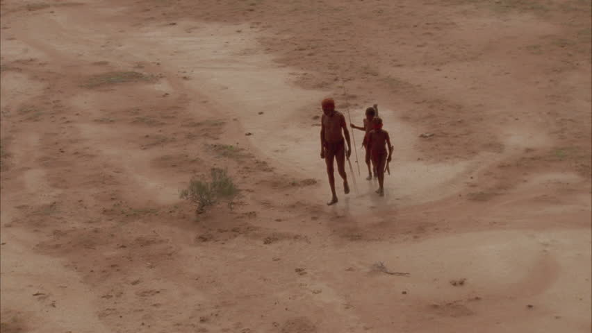 NORTHERN TERRITORY, AUSTRALIA - CIRCA 1996- Aborigines walk across red sand circa 1996 in North Territory.
