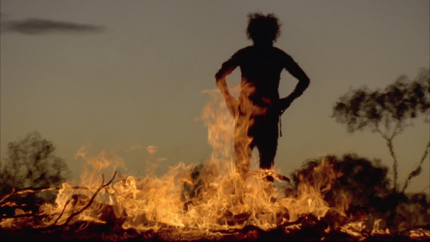 NORTHERN TERRITORY, AUSTRALIA - CIRCA 1996- Man in dark silhouette with blazing fire in front of him. His hair is wild circa 1996 in North Territory.