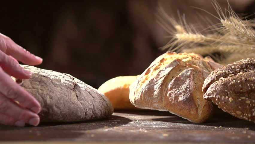 Bakery Bread on a Wooden Table. Various Bread and Sheaf of Wheat Ears. Man hands puts bread on the table. Slow motion 1080 HD video footage. Slow-mo. Slowmo high speed camera shot 240 fps. Dolly shot