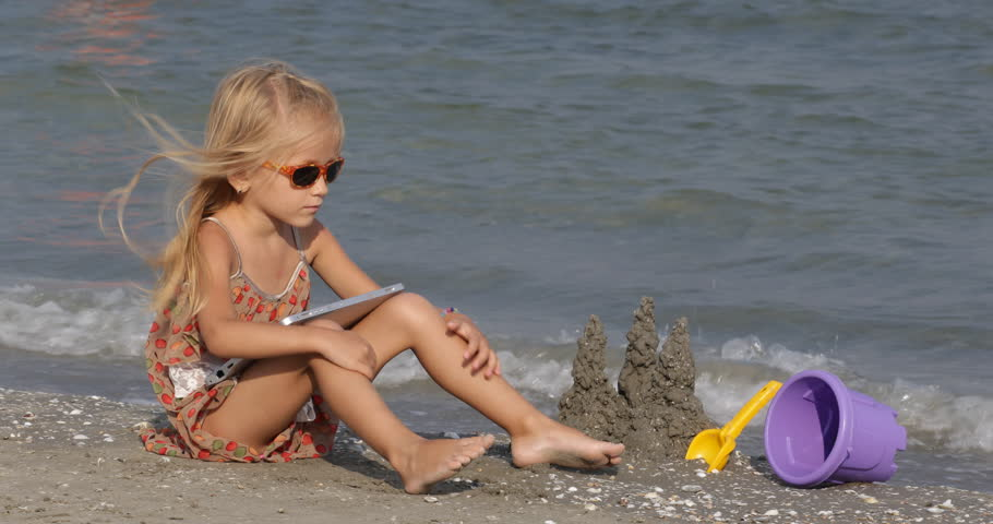 K View Caucasian Child On Beach Playing On Internet With Wireless Tablet On Sand Castle Near Sea Water Blonde Little Girl Working Surfing Pc