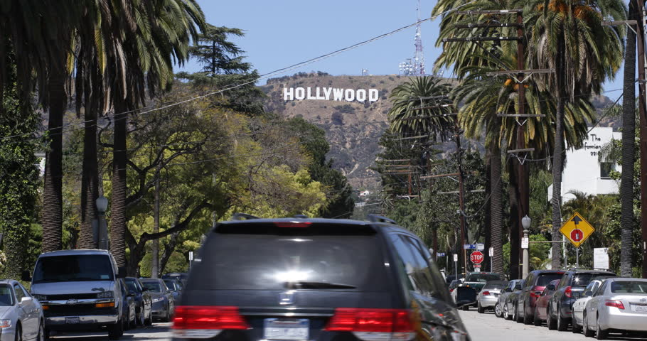 LOS ANGELES, USA - APRIL 3, 2013 Hollywood Sign on the Hillsides of Los Angeles Hills Street Cars Passing Sunny Day Sunlight ( Ultra High Definition, Ultra HD, UHD, 4K, 2160P, 4096x2160 )
