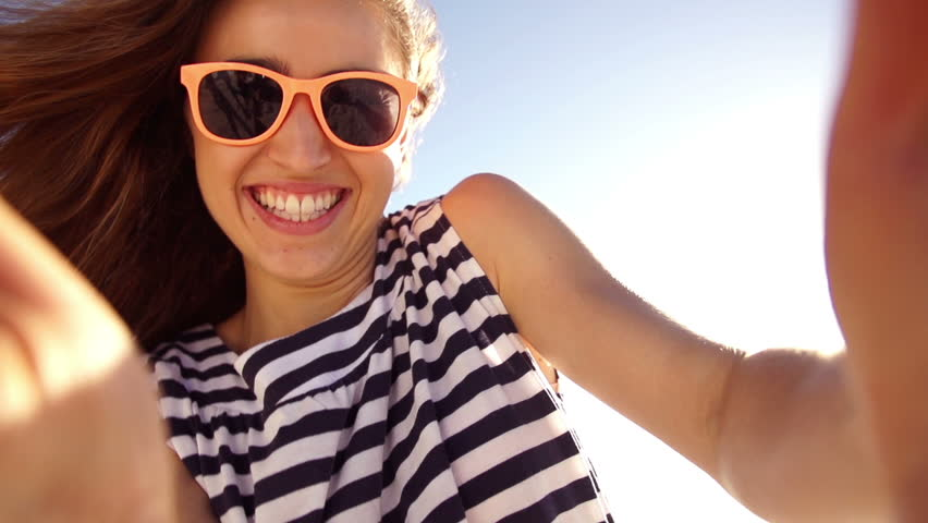 Young woman taking selfie on the beach in slow motion