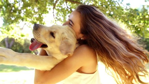 Young woman spinning with her labrador dog in slow motion