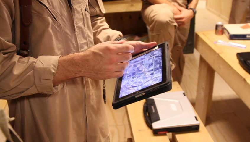 Afghanistan, Circa 2011: USAF airman in uniform talks with computer tablet in his hand with screen showing terrain information