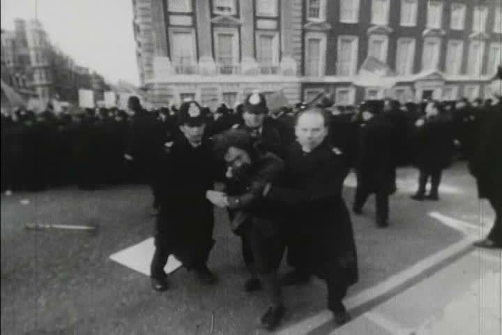 CIRCA 1970s - 1970s black and white footage of people protesting the Vietnam War and being contained by police in London, England