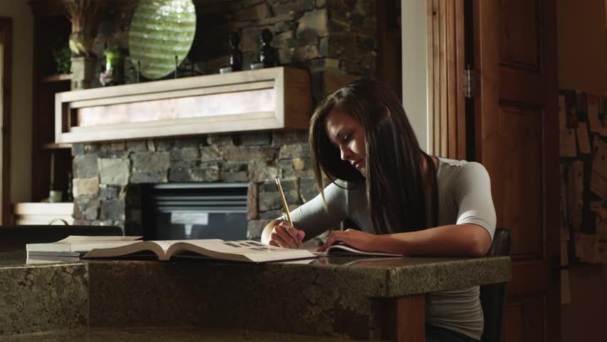 Medium Shot Teenage (16-17) girl doing homework at home | Shutterstock HD Video #6294263