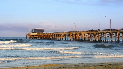 Balboa pier in Newport Beach, California during sunrise shows a beautiful orange light bouncing off the pier and waves moving towards shore.