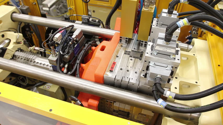 A wider shot cuts to a close-up of an injection molding machine in a factor | Shutterstock HD Video #6311003
