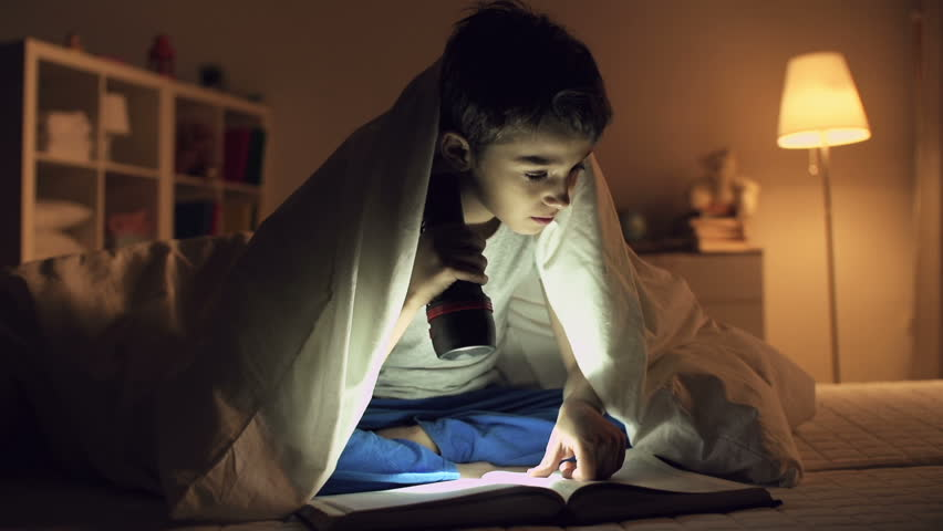 Static shot of boy sitting under blanket and reading a book