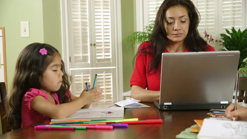 A single mom worries about how to pay bills while children color peacefully unaware of the stress she is feeling.