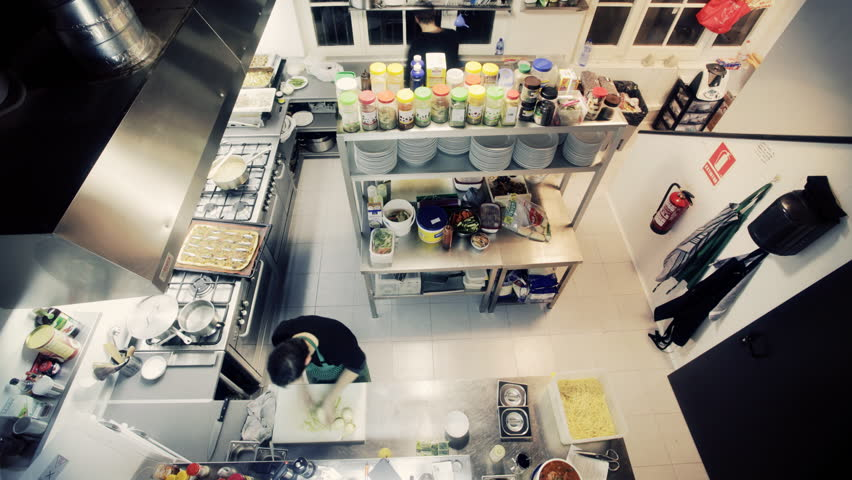 timelapse shot looking down on two chefs preparing food in a busy restaurant kitchen