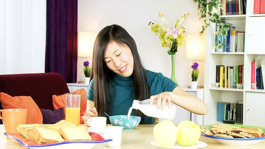 Asian woman poring milk into cereals for breakfast at home