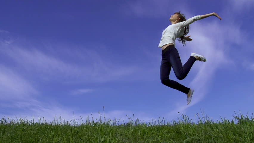 Young active attractive woman is having fun outdoors on a sunny day. Woman is running and jumping on a meadow in summer. Slow motion filmed at 250 fps.