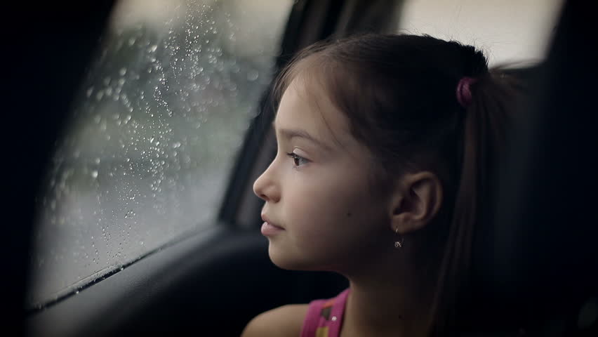 a sad seven year old asian girl sits by a window watching