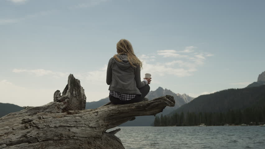 Medium shot of young woman drinking coffee on log at lake / Redfish Lake, Idaho, United States