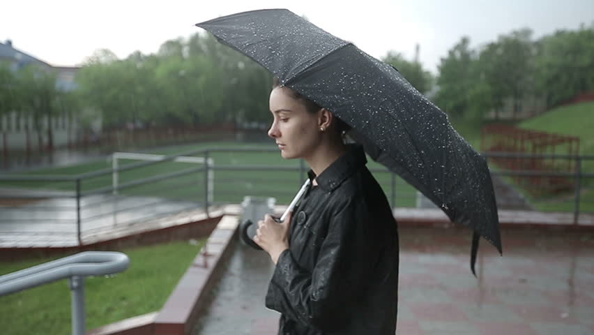 Lonely sad woman with a black umbrella walks down the street in heavy rain. Slow motion