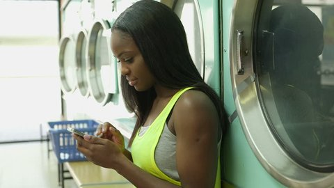 A Young Woman sits with her smartphone in a Launderette and in the background a Young Woman uses a Washing Machine
