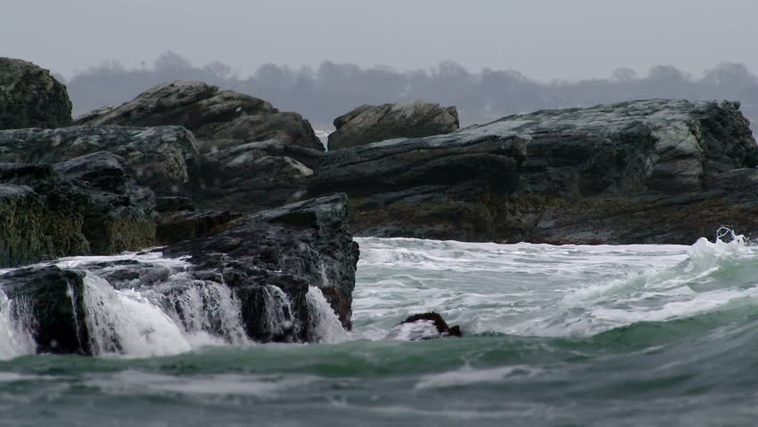 Big heavy waves crash into a rocky cliff and spray mist everywhere, in slow motion