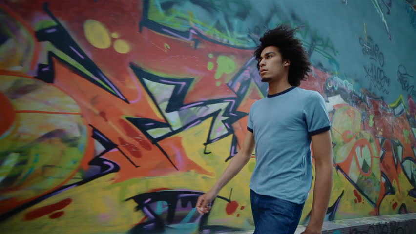 young, handsome man walking along the wall.  he looks indifferent, apathetic and lonely