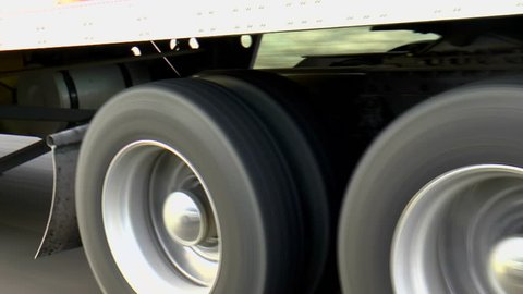 Semi, commercial eighteen-wheeler truck wheel caps reflect passing car as tires spin along interstate highway. 1080p