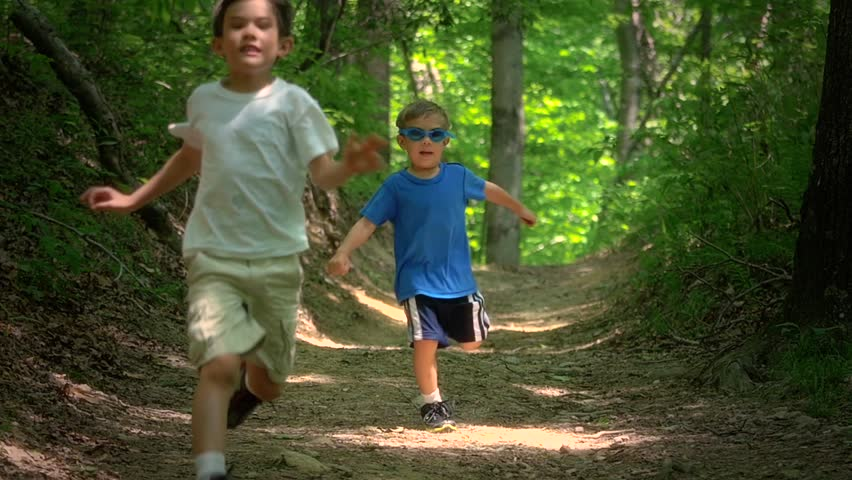Two boys running in the forest together laughing and playing and jumping in slow motion. full hd video clip