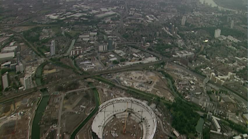 LONDON, UK - MARCH 28: Aerial view of Canary Wharf from a distance, zooming out to reveal the 2012 London Olympic Stadium under construction on March 28, 2010 in London, UK. | Shutterstock HD Video #6493943