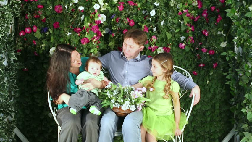 Family of four sits on white openwork garden bench in arbour.. suburban life.    Shutterstock HD Video #6499079