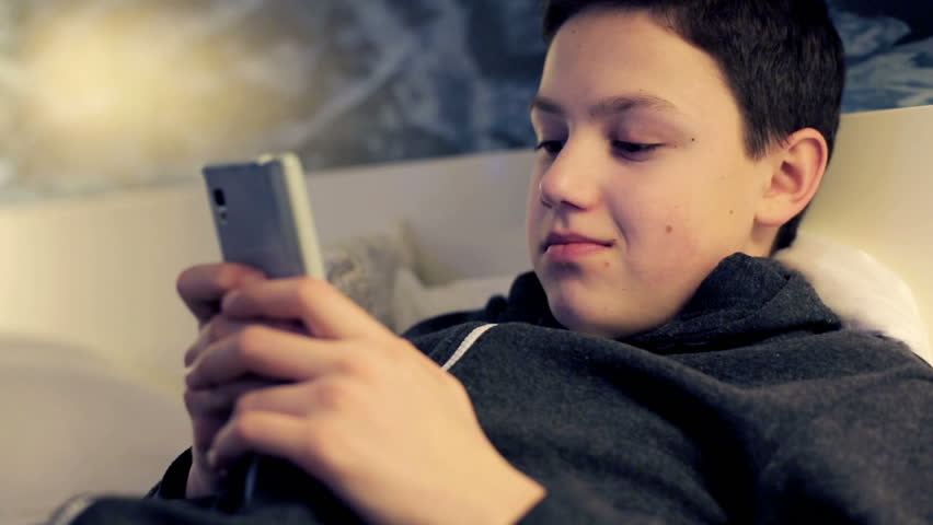 Young boy with smartphone lying on bed at night    Shutterstock HD Video #6510596