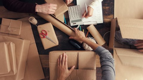 Hands wrapping brown paper packages for postage from above high angle