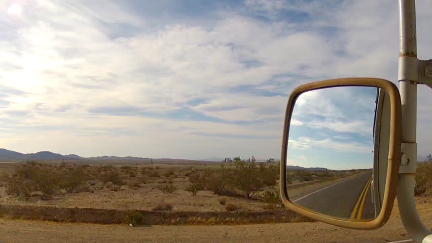 The side view of a driver of a truck or RV as he rolls through the Mojave Desert on Route 66 between Victorville and Barstow California.
