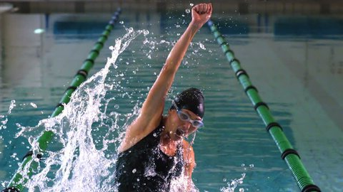 Fit swimmer jumping and cheering in swimming pool in slow motion