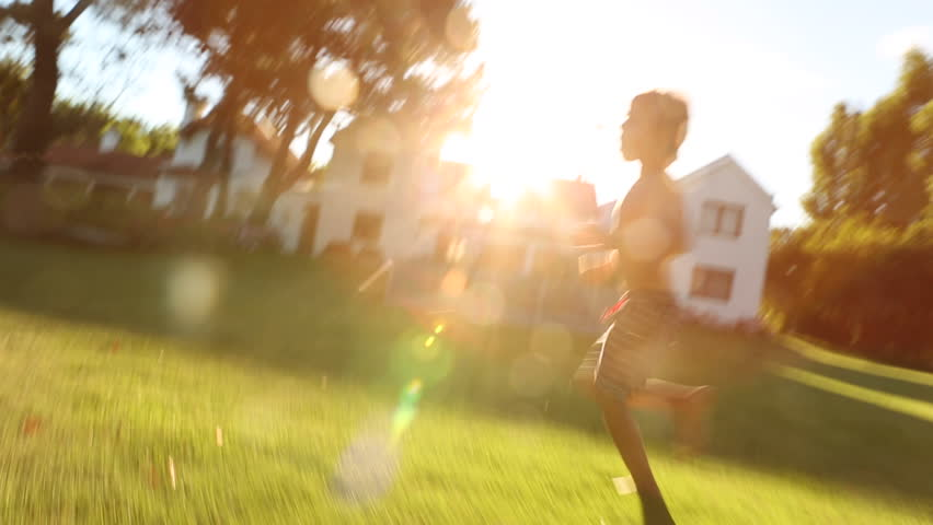 Boy Running during golden hour light. Energetic shot of a kid running during his summer time holidays. Child filled with enthusiasm running with sunlight flare hitting the lens. Beautiful golden hour