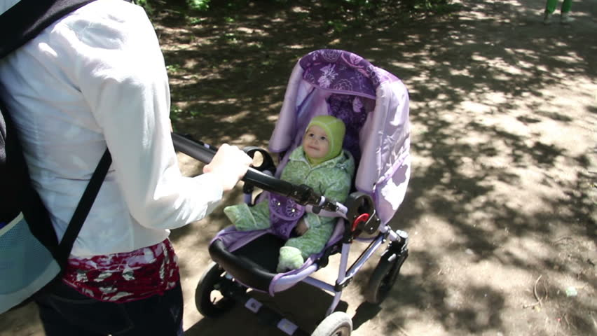 Mother walking with baby with in the stroller in park   Shutterstock HD Video #6594113