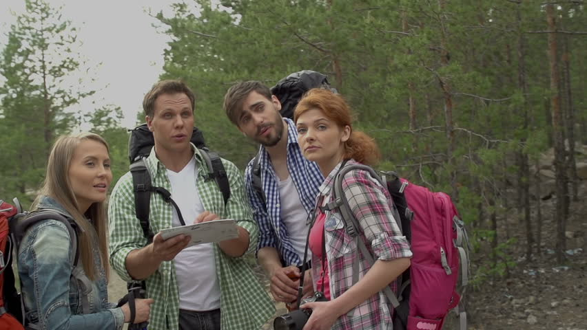 Pan of disoriented trekkers standing in the middle of the woods and studying map | Shutterstock HD Video #6611753