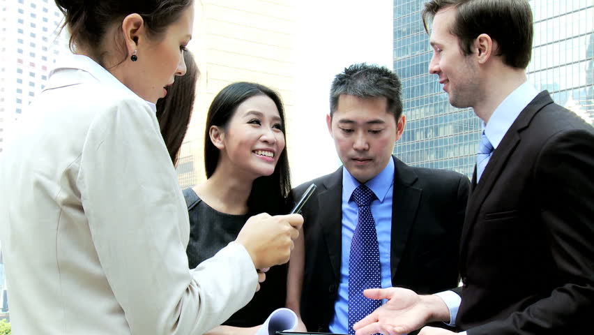 Confident young male female Asian Chinese Caucasian business colleagues discussing client information wireless tablet technology hot spot outside city downtown | Shutterstock HD Video #6646754
