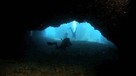 Scuba divers swimming through long dark passage underwater beneath Gato Island, Philippines