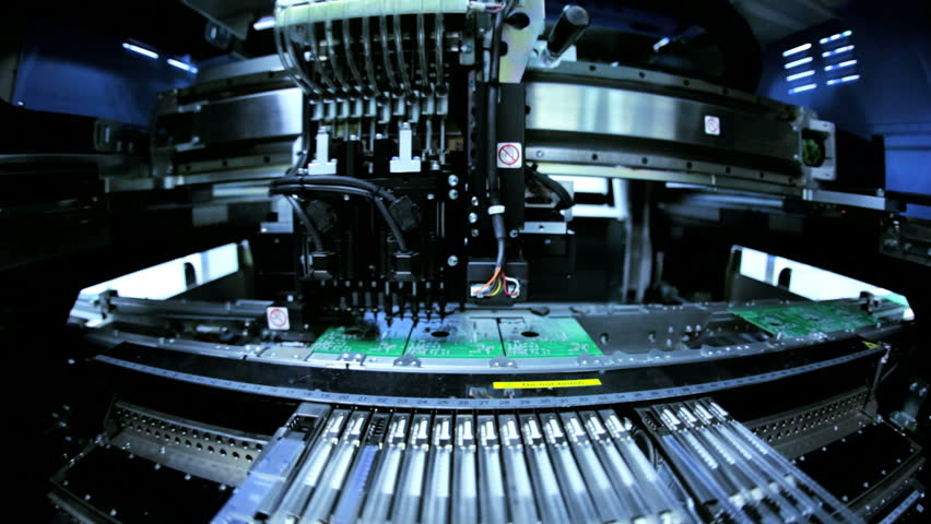 Close up of automated machine manufacturing PCBs operated by Chinese worker, Mainland China, East Asia