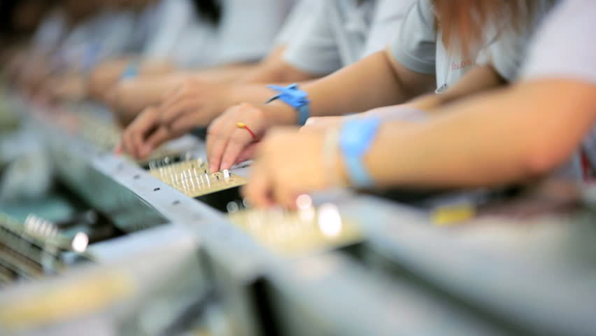Close up Chinese skilled workers producing PCB boards for electronic equipment on factory production line, China