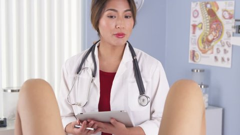 Asian OBGYN talking to patient in exam room