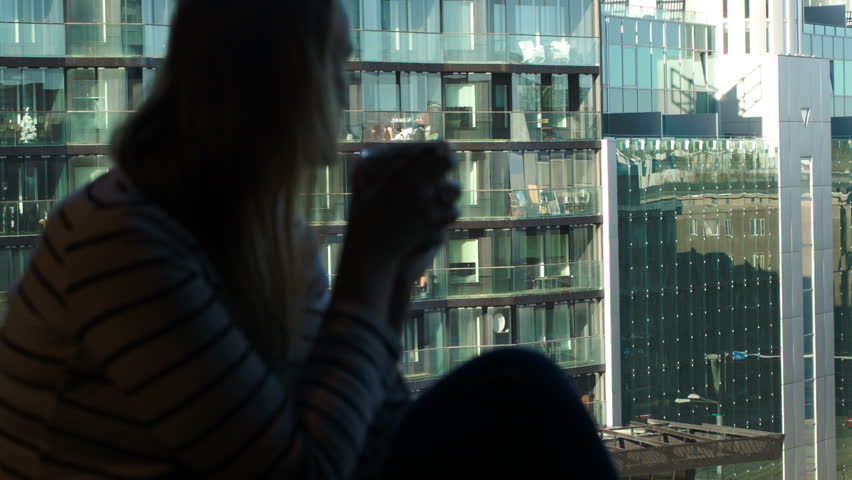 Dolly shot of a woman drinking coffee sitting by the window with city view. Modern glass building shining in the sun. Focus on the city view