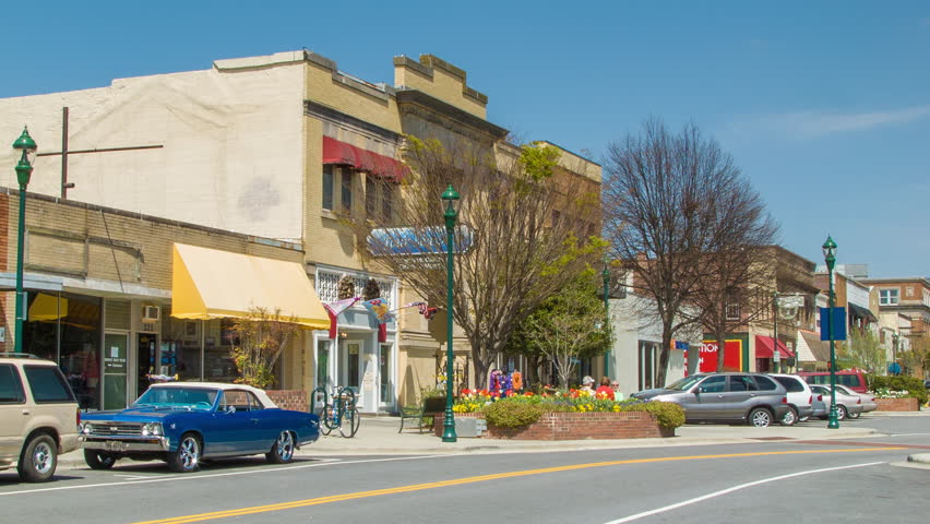 Cars Driving Down Main Street in Downtown Hendersonville North Carolina Featuring Historic Brick Buildings on a Perfect Sunny Day in the Appalachian Mountains of WNC. Small town America establishing shot.