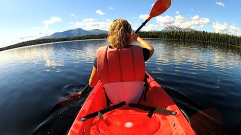 Canoeist kayaking across wilderness lake, USA - Confident canoeist kayaking across wilderness lake, Pacific Northwest, USA